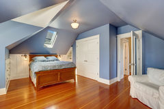 Lavender interior of attic bedroom with queen size bed. And hardwood floor. Also white doors closet and built-in cabinets. Northwest, USA royalty free stock image
