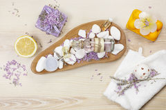 Lavender and lemon aromatherapy. Natural handmade lavender oil, soaps with bath salt, foaming bath bomb, lemon and lavender on wooden background Royalty Free Stock Image