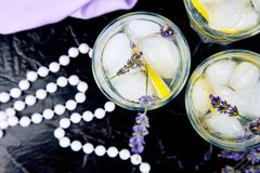 Lavender lemonade with lemon and ice on black background. Detox water. Summer drink. Diet cocktail. Beautiful. Top view. Copy. Space royalty free stock images