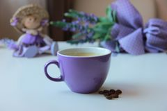 Lavender and lilac cup of coffee. In a pattern purple, homely summer comfort with a bouquet of lavender doll and a cup of coffee, lunch in a beautiful place, a royalty free stock image