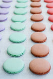 Lavender, mint, caramel and pink macaroon cups over baking paper Stock Image