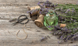 Lavender oil with fresh flowers and scissors on wooden backgroun Royalty Free Stock Photo