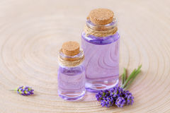 Lavender oil in glass bottles and fresh lavender flowers on stump and wooden background Royalty Free Stock Images