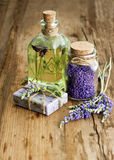 Lavender oil, herbal soap and bath salt. Essential lavender oil, herbal soap and bath salt with fresh flowers on wooden background. selective focus Royalty Free Stock Image