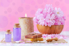 aroma oil, soap, salt, fresh flowers, candle, on pink, for spa and wellness Royalty Free Stock Photo