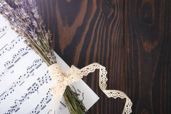 Lavender and paper music notes on old wooden background in vintage style. Royalty Free Stock Images