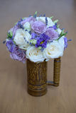 Lavender and roses with purple hues floral arrangement set in a decorated vase with handle. Floral arrangement, essential accessory for the bride, details, ideas Stock Photos