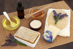 Lavender Skin Care. Lavender flower skin care with honey, almond oil, moisturising cream, soap, essential oil, exfoliating scrub and flannel on bamboo over oak Royalty Free Stock Image