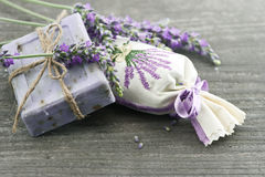 Lavender soap with fresh flowers. Lavender soap and scented sachets with fresh flowers over wooden background royalty free stock photography