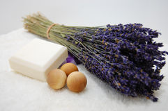 Lavender in the Spa. A bouquet of dry lavender, natural soaps, and three aromatic wooden balls on a soft white towel with a white background Stock Images