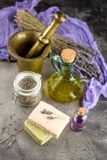 Lavender spa products. Bouquet of dry lavender,, a copper mortar with a pestle, pieces of homemade soap and oil for massage in glass bottles. Set of lavender spa stock photo