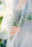 Lavender Wedding bouquet in hands of the bride under veil in pal Stock Photo