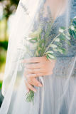 Lavender Wedding bouquet in hands of the bride under veil in pal Royalty Free Stock Photography