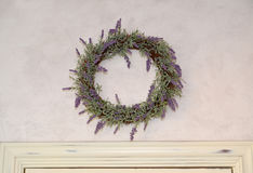The lavender wreath hangs on a wall over a white door Stock Photography