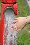 Lavez les mains sous le jet de l'eau d'une bouche d'incendie Image libre de droits