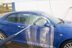 Lavez un véhicule dans la lave-auto avec de l'eau Photo stock