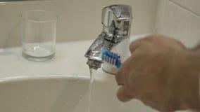 Lavi lo spazzolino da denti sotto acqua corrente stock footage
