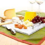 Lavish marble serving tray with cheese, crackers, grapes, apricots, bread sticks,and cheese knives. Stock Image