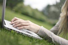 Lavorando ad un computer portatile nell'erba Immagini Stock Libere da Diritti