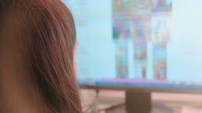 Lavorando al computer Le pagine di Internet irriconoscibili di lettura rapida della giovane donna in schermo e fa gli acquisti ne archivi video