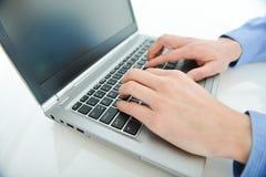 Lavorando al computer portatile Immagini Stock Libere da Diritti