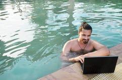 Lavorando al computer portatile dalla piscina fotografia stock libera da diritti