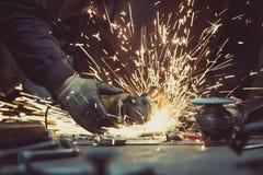 Lavorando al taglio del tubo del metallo con una smerigliatrice di angolo tagliente con la lama circolare ed alla generazione sci Fotografie Stock