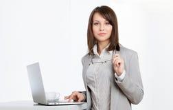 Lavorando alla donna di affari di calcolatore al offi Immagine Stock