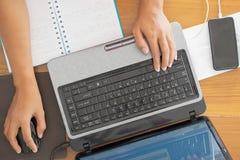 Lavorando allo scrittorio con il taccuino del computer Immagini Stock
