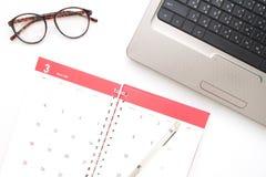 Lavorando con il computer portatile e le attività mensili d'organizzazione ed il ap fotografie stock