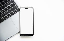 Lavorando con Smartphone sul computer portatile immagini stock