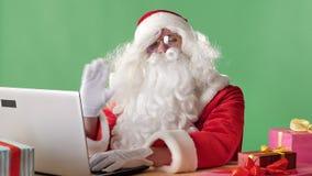 Lavorare di seduta serio di Santa Claus al computer portatile, scrivere, esaminare macchina fotografica ed ondeggiare la sua mano archivi video