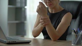 Lavorare femminile al computer portatile, dolore ritenente del polso, osteoartrite, infiammazione unita archivi video