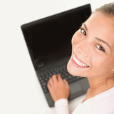 Lavorare sorridente della donna del computer portatile al pc del computer Fotografie Stock Libere da Diritti