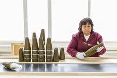 Lavoratore ad una catena di montaggio nella fabbrica della munizione Immagini Stock