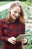 Lavoratore agricolo femminile che utilizza la compressa di Digital nel campo Fotografie Stock Libere da Diritti