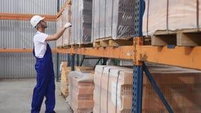 Lavoratore ai mattoni rossi del controllo del magazzino impilati nei cubi blocchi rossi di mattoni in azione Mattoni del magazzin stock footage