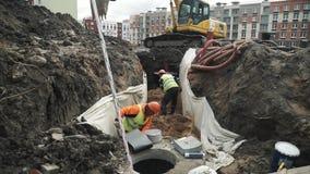 Lavoratore in anello concreto di scavatura della botola della camera della sabbia del casco arancio in fossa stock footage