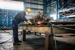 Lavoratore asiatico che per mezzo della taglierina del plasma di CNC fotografia stock
