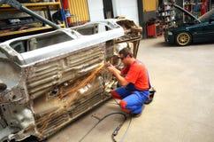 Lavoratore automobilistico che frantuma l'automobile Fotografia Stock