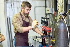 Lavoratore barbuto che per mezzo della capsulatrice della bottiglia Immagini Stock