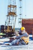 Lavoratore barbuto in maglia riflettente ed elmetto protettivo che si siedono al cantiere ed allo sguardo fotografia stock