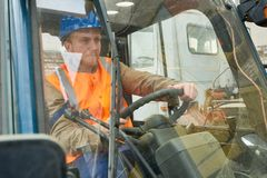 Lavoratore bello che conduce carrello elevatore fotografia stock