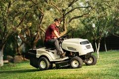 Lavoratore bello che usando giro-sulla falciatrice da giardino del trattore Fotografie Stock