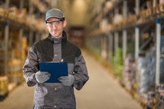 Lavoratore caucasico sorridente con la lavagna per appunti in magazzino Fotografie Stock Libere da Diritti
