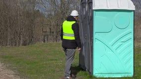 Lavoratore che aspetta vicino alla toilette portatile video d archivio