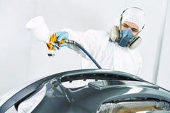Lavoratore che dipinge il paraurti automatico dell'automobile Immagini Stock Libere da Diritti
