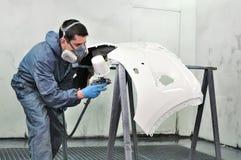Lavoratore che dipinge un paraurti dell'automobile. Fotografie Stock