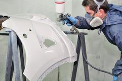 Lavoratore che dipinge un paraurti dell'automobile. Fotografie Stock Libere da Diritti