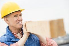 Lavoratore che distoglie lo sguardo mentre portando plancia di legno Immagini Stock Libere da Diritti